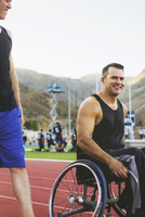 Paraplegic athlete in wheelchair and friend on track
