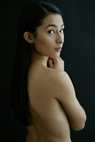 Nude Hispanic woman looking over shoulder
