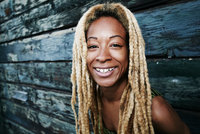 Black woman smiling at wooden wall