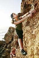 Women climbing rock formation