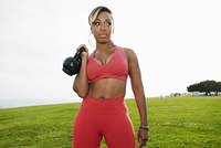Black woman lifting weights in field