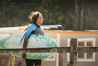 African American woman carrying surfboard outdoors