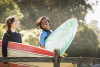 Women carrying surfboards outdoors