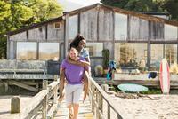 Man carrying girlfriend piggyback on wooden deck