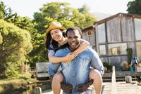 Man carrying girlfriend piggyback outdoors