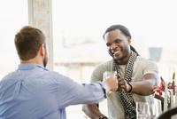 Smiling men toasting indoors