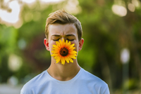 Caucasian teenage boy holding sunflower in mouth