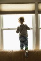 Caucasian boy looking out window