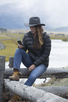 Caucasian woman using cell phone at rural river
