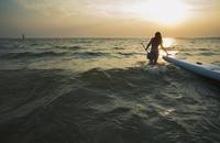 Woman pulling paddleboard in lake
