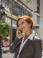 Caucasian businesswoman talking on cell phone in city