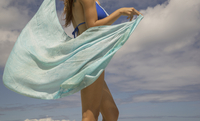 Hispanic woman holding sarong blowing in wind
