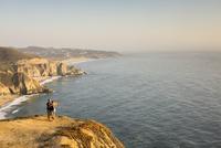 Caucasian couple on cliff admiring seascape