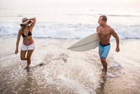Caucasian couple in waves on beach