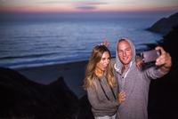 Caucasian couple taking selfie at beach