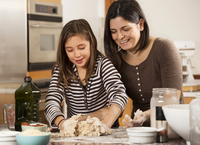 Hispanic mother and daughter baking in kitchen