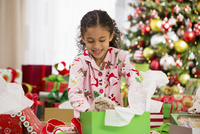 Hispanic girl opening Christmas gift