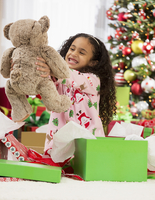 Hispanic girl opening teddy bear Christmas gift