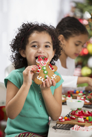 Hispanic girl eating gingerbread cookie