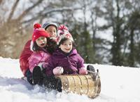Hispanic family sledding in snow