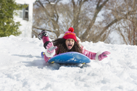 Hispanic girl sledding in snow