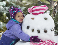 Black girl hugging snowman outdoors