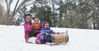 Black sisters sledding in snow