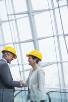 Architects shaking hands near window