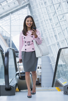 Asian businesswoman using cell phone in airport
