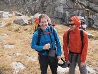 Caucasian hikers smiling on hillside