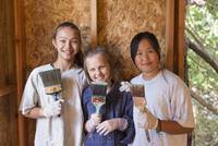 Smiling girls painting house