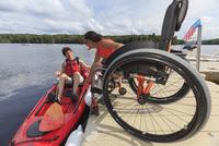 Caucasian instructor helping paraplegic woman with kayak