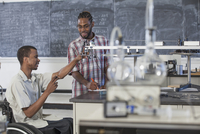 Paraplegic student working with classmate in science classroom