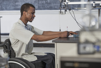 African American paraplegic student working in science classroom
