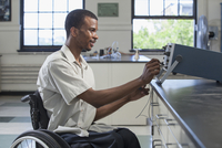 African American paraplegic student performing experiment in science classroom