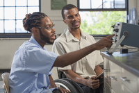 Paraplegic student and classmate working in science classroom
