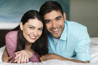 Hispanic couple smiling on bed