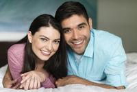 Hispanic couple smiling on bed