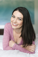 Hispanic woman smiling on bed