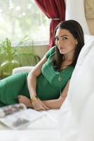 Hispanic woman sitting on sofa