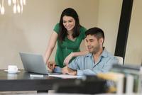 Hispanic couple using laptop at table