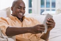 Black man using digital tablet on sofa