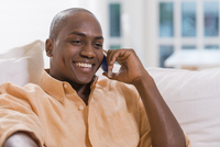 Black man talking on cell phone on sofa