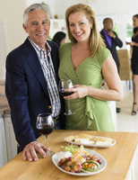 Caucasian couple drinking wine at party