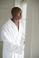 Black man in bathrobe looking out window