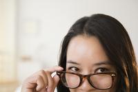 Chinese woman peering over eyeglasses
