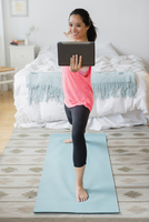 Chinese woman practicing yoga with digital tablet