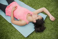 Chinese woman laying on yoga mat in grass