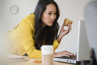 Chinese businesswoman using laptop and eating