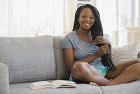 Black woman reading on sofa